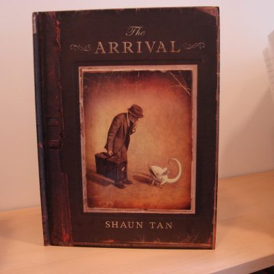 "Cover the the book ""The Arrival"" with the title, author's name and an image featuring a man (an immigrant) with a hat and a suitcase staring down at a mouse-like creature"