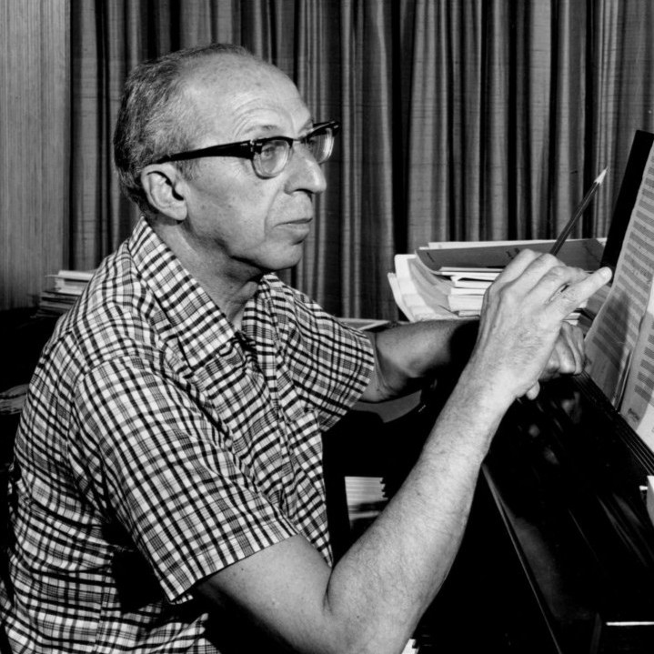 A black and white photograph of Aaron Copland seated at a piano, writing on sheet music with a pencil.