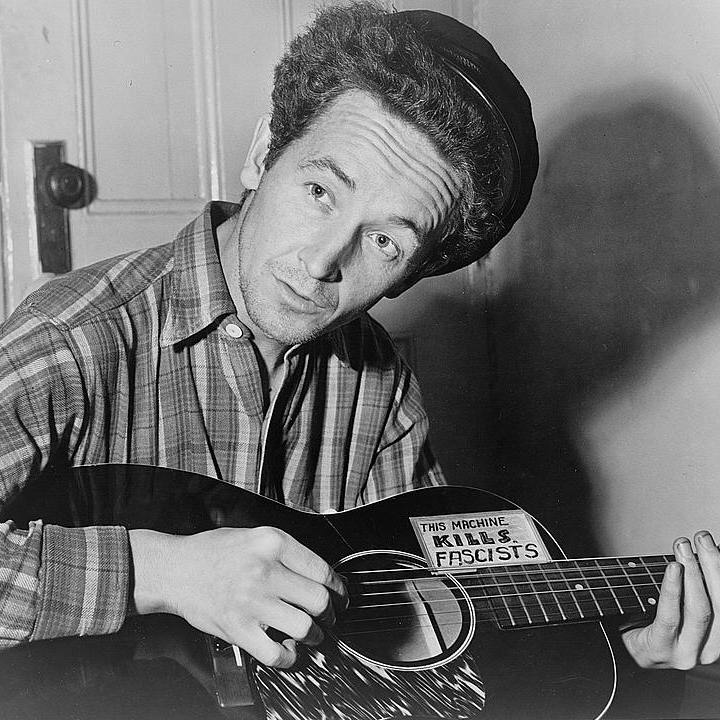 "A black and white photo of Woodie Guthrie playing the guitar. On his guitar a sticker reads ""This Machine Kills Fascists."""