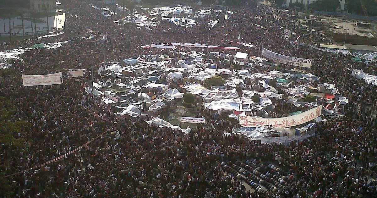 An aerial photograph of a large crowd of people gathered in Tahrir Square.